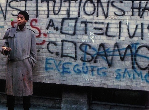 Jean-Michel Basquiat posing next to SAMO graffiti