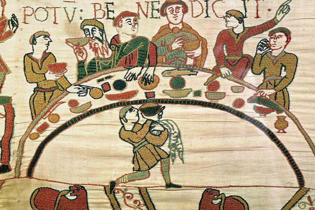 Norman's first meal in England, at the center is Bishop Odo, who gazes out as he offers a blessing over the cup in his hand.(detail), Bayeux Tapestry, c. 1070, embroidered wool on linen, 20 inches high (Bayeux Museum)