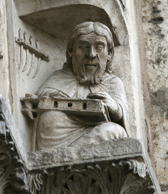 A scribe identified as Priscian or Donatus, part of a series of liberal arts and scribes on the archivolt of the right bay, West portal, Chartres, c.1150), photo Holly Hayes
