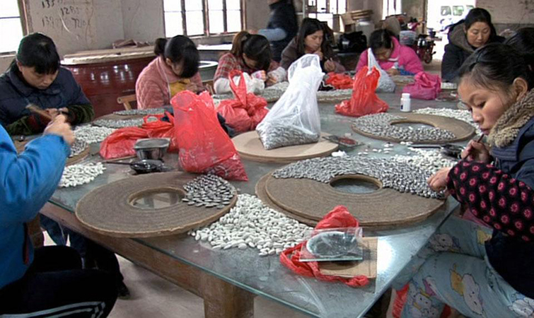 Some of the 3000 highly skilled craftspeople from Jingdezhen hired to create and paint porcelain sunflower seeds