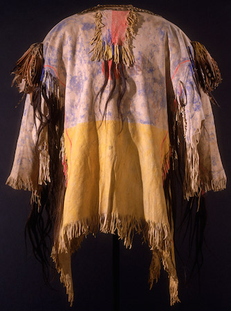 Lakota War Shirt, associated with Tashunca-uitco (Crazy Horse, Ogala Lakota), c. 1870s (South Dakota), hide, human- and horsehair, quill, pigment, woodpecker feathers, arrowhead, cocoon (NMAI, NYC)