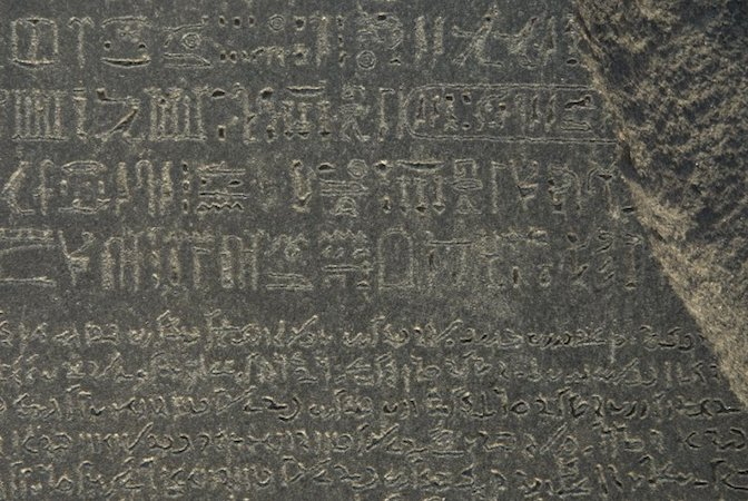 The Rosetta Stone, 196 B.C.E., Ptolemaic Period, 112.3 x 75.7 x 28.4 cm, Egypt © Trustees of the British Museum. Part of grey and pink granodiorite stela bearing priestly decree concerning Ptolemy V in three blocks of text: Hieroglyphic (14 lines), Demotic (32 lines) and Greek (53 lines).