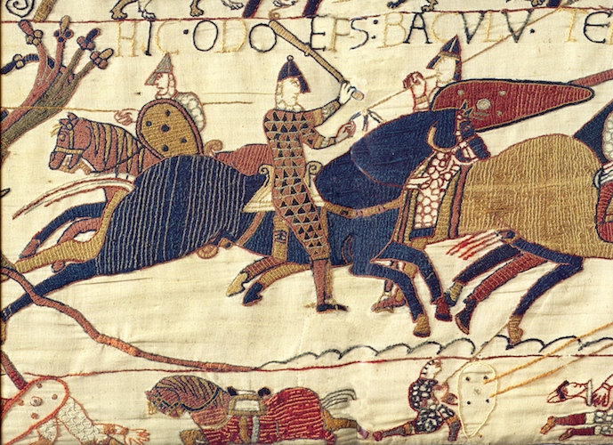 "The inscription above Odo (partially cut off in the reproduction above) reads, ""Here, Odo the Bishop, with a staff (baculum) encourages the young warriors,"" Bayeux Tapestry, c. 1070, embroidered wool on linen, 20 inches high (Bayeux Museum)"