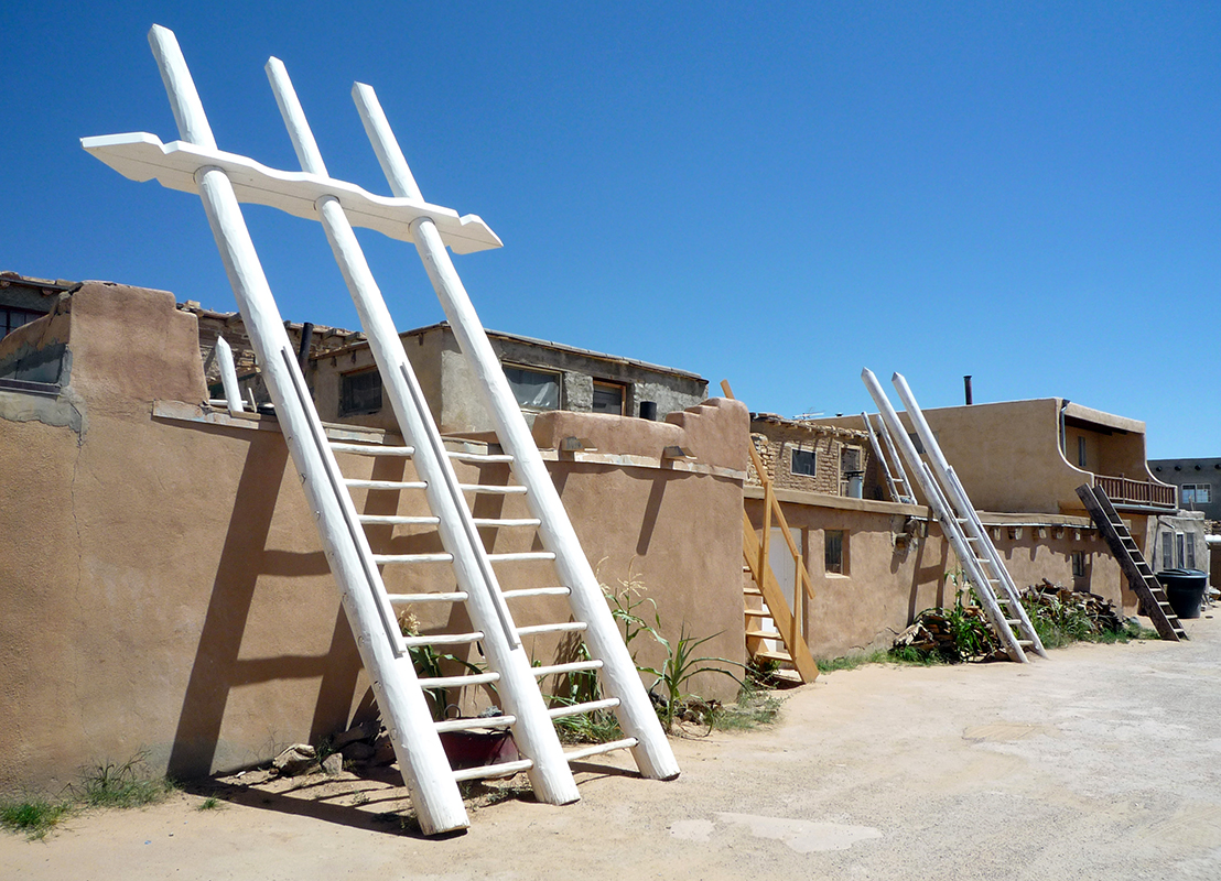 Acoma Pueblo street with adobe buildings and ladders that lead to the upper story entrances to kivas (sacred ceremonial spaces)
