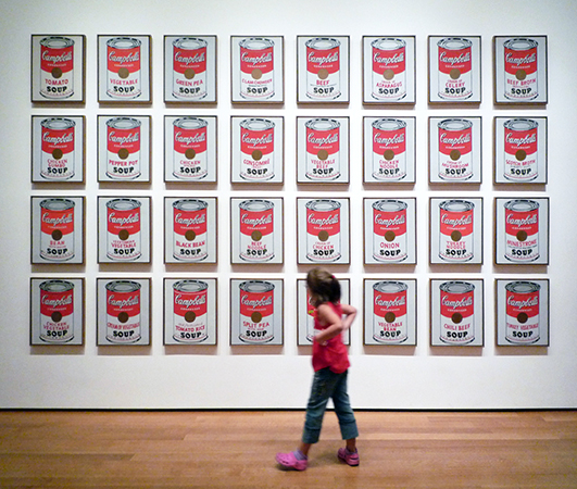 Girl Looking at Andy Warhol, Campbell's Soup Cans, 1962, synthetic polymer paint on 32 canvases, each 20 x 16 inches (The Museum of Modern Art) (photo: Steven Zucker)