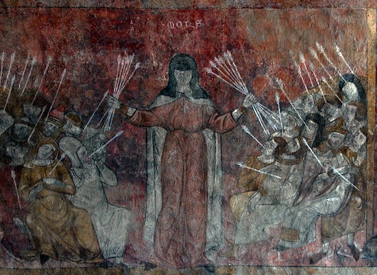 "Fresco in the former Abbey of Saint-André-de-Lavaudieu, France, 14th century, depicting the plague personified as a woman, she ""carries arrows that strike those around her, often in the neck and armpits—in other words, places where the buboes commonly appeared"" (see Franco Mormando, Piety and Plague: from Byzantium to the Baroque, Truman State University Press, 2007)."