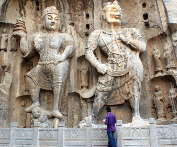 Vaiśravana, one of The Four Heavenly Kings, is on the left (indicated by the stupa in his right hand). Vajrapāṇi (on the right) are spiritual beings that wield the thunderbolt, 673-675 C.E., Tang dynasty, limestone, Luoyang, Henan province, (photo: Sanjay P. K. CC BY-NC-ND 2.0)
