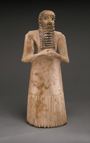 <em>Standing Male Worshipper (votive figure)</em>, c. 2900-2600 B.C.E., Eshnunna (modern Tell Asmar, Iraq), gypsum alabaster, shell, black limestone, bitumen, 11 5/8 x 5 1/8 x 3 7/8″ / 29.5 x 10 cm, Sumerian (The Metropolitan Museum of Art, New York City)
