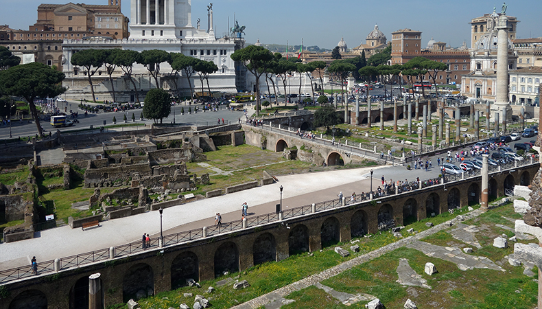 View of the Forum of Trajan, c. 112 C.E.. Later medieval walls can be seen amidst the grass on the left; the upright columns of the Basilica Ulpia can be seen on the right in front of the larger Column of Trajan